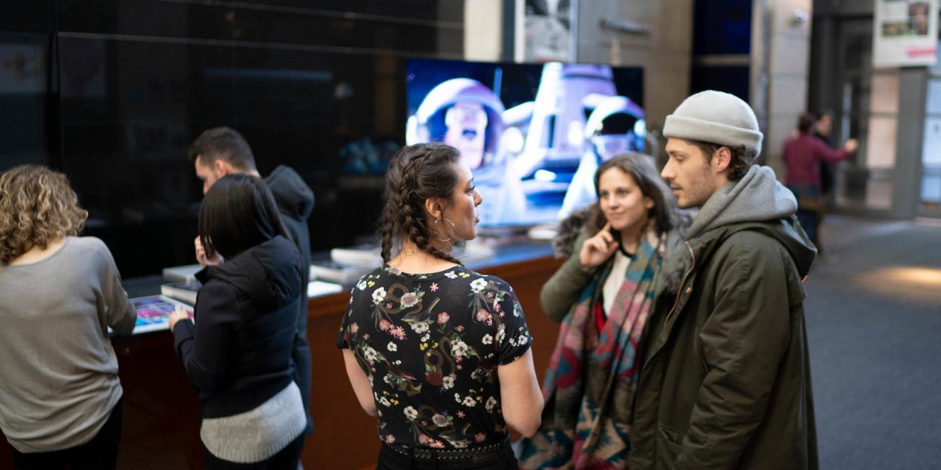 Personnes discutant dans le hall du bâtiment ExCentris ESMA