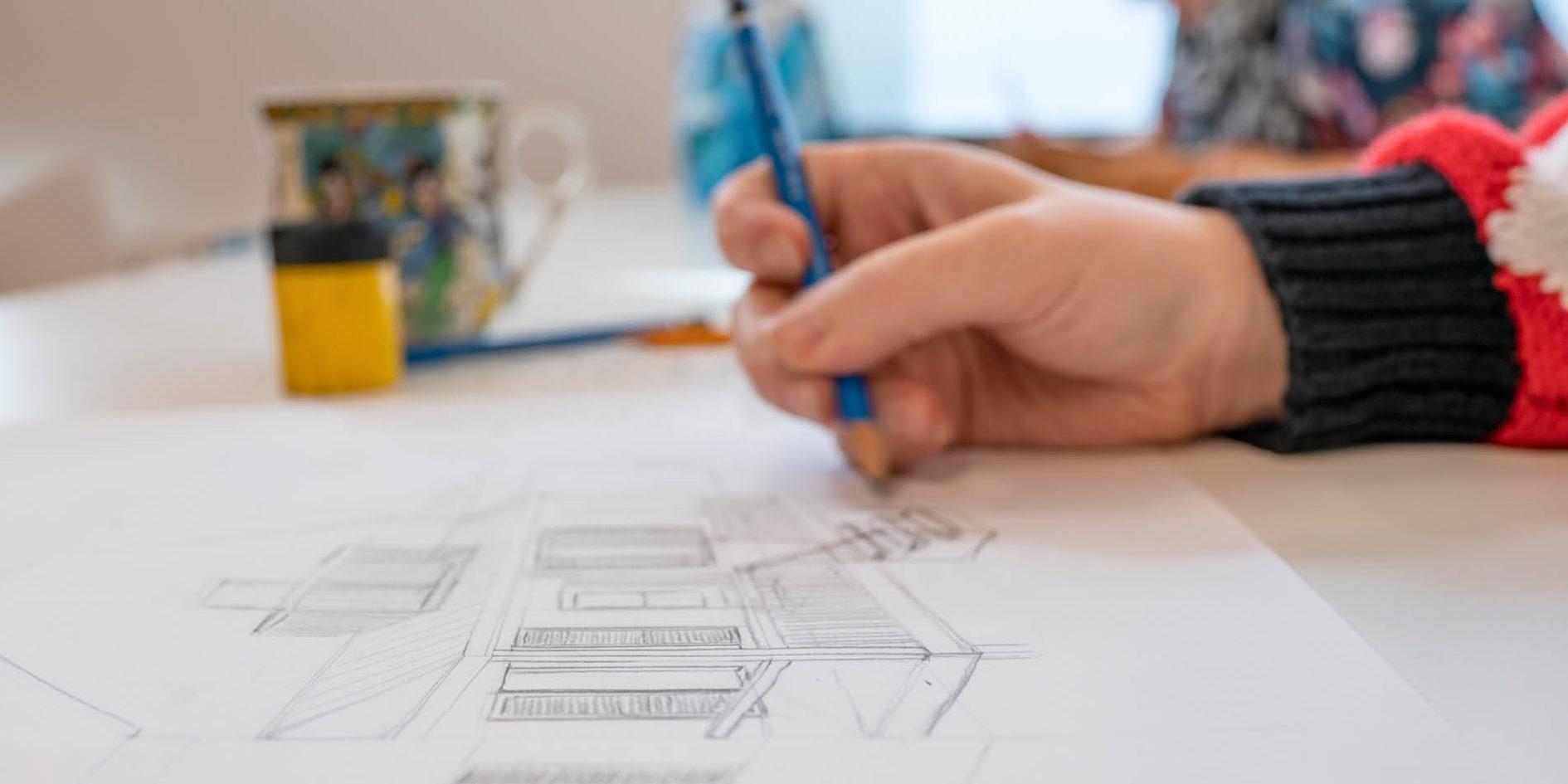 Etudiant dessinant sur une feuille de papier