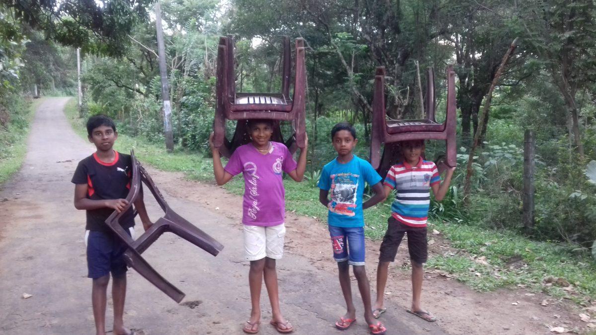 Enfants sri lankais portant des chaises en plastique